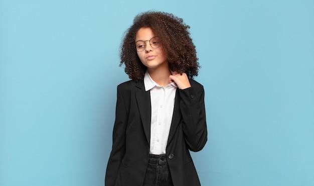Ładna nastolatka afro czuje się zestresowana, niespokojna, zmęczona i sfrustrowana, ciągnie za szyję koszuli, wygląda na sfrustrowaną problemem. humorystyczny pomysł na biznes