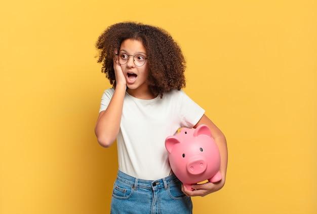 Ładna nastolatka afro czuje się znudzona, sfrustrowana i senna po męczącym, nudnym i żmudnym zadaniu, trzymając twarz w dłoni. koncepcja oszczędności