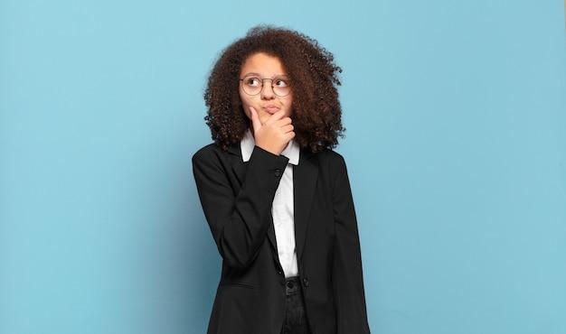 Ładna nastolatka afro myśląca, wątpiąca i zdezorientowana, z różnymi opcjami, zastanawiająca się, jaką decyzję podjąć. humorystyczny pomysł na biznes