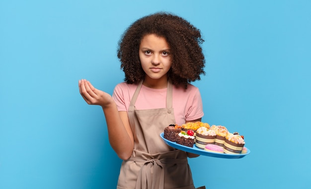 Ładna nastolatka afro robi gest kaprysu lub pieniędzy, każąc spłacić długi!. humorystyczna koncepcja piekarza