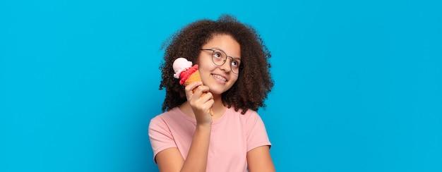 Ładna nastolatka afro uśmiecha się radośnie i marzy lub wątpi, patrząc w bok. koncepcja lodów sumerskich