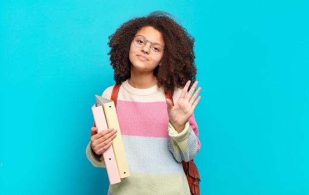 Ładna nastolatka afro uśmiechająca się radośnie i wesoło, machająca ręką, witająca i witająca lub żegnająca się. koncepcja studenta
