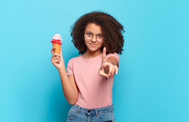 Ładna nastolatka afro uśmiechnięta dumnie i pewnie, triumfalnie tworząca pozę numer jeden, czując się jak lider. koncepcja lodów sumer