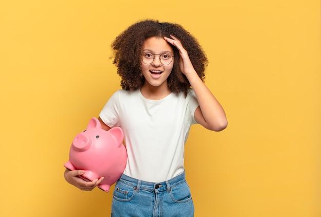 Ładna nastolatka afro uśmiechnięta i wyglądająca przyjaźnie, pokazująca numer jeden lub pierwszy z ręką do przodu, odliczając w dół. koncepcja oszczędności