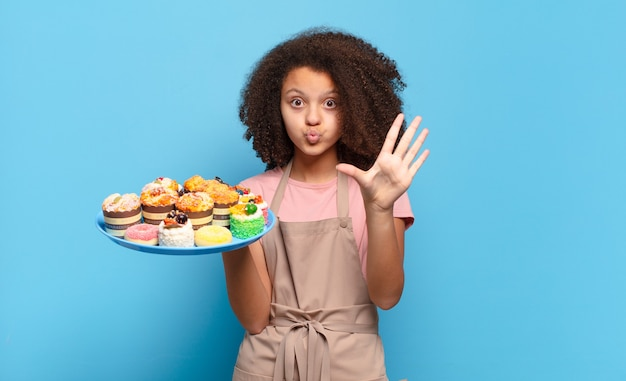 Ładna nastolatka afro, uśmiechnięta i wyglądająca przyjaźnie, pokazująca numer pięć lub piąty z ręką do przodu, odliczający w dół. humorystyczny koncepcja piekarza