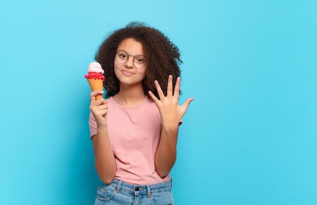 Ładna nastolatka afro, uśmiechnięta i wyglądająca przyjaźnie, pokazująca numer pięć lub piąty z ręką do przodu, odliczający w dół