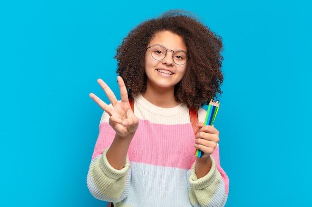 Ładna nastolatka afro uśmiechnięta i wyglądająca przyjaźnie, pokazująca numer trzy lub trzeci z ręką do przodu, odliczając w dół. koncepcja studenta