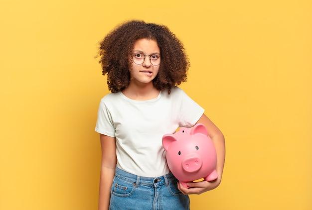 Ładna nastolatka afro uśmiechnięta radośnie, czująca się szczęśliwa i pokazująca koncepcję w przestrzeni kopii dłonią. koncepcja oszczędności