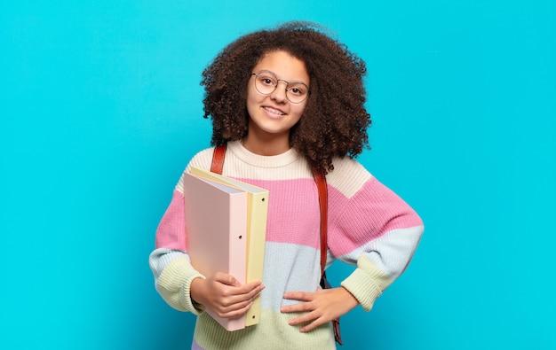 Ładna nastolatka afro uśmiechnięta radośnie z ręką na biodrze i pewna siebie, pozytywna, dumna i przyjazna. koncepcja studenta