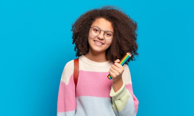 Ładna nastolatka afro uśmiechnięta radośnie, z ręką na biodrze, pewna siebie, pozytywna, dumna i przyjazna