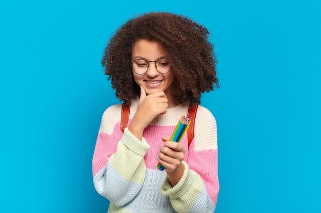 Ładna nastolatka afro, uśmiechnięta z radosną, pewną siebie miną, z ręką na brodzie, zastanawiająca się i spoglądająca w bok. koncepcja studenta