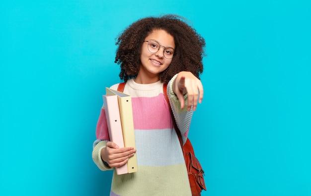 Ładna nastolatka afro wskazująca z zadowolonym, pewnym siebie, przyjaznym uśmiechem, wybiera ciebie. koncepcja studenta