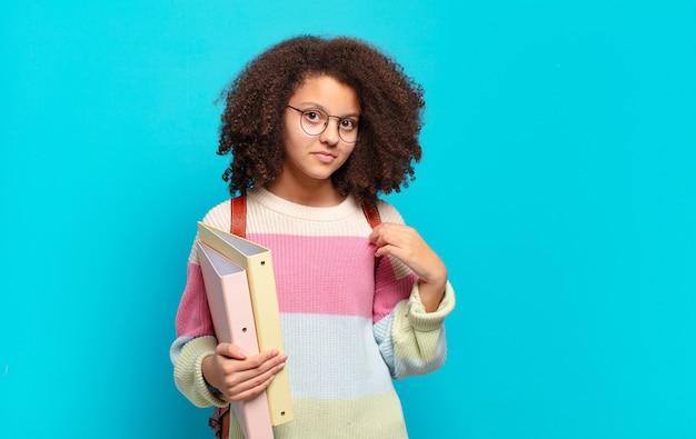 Ładna nastolatka afro wyglądająca arogancko, odnosząca sukcesy, pozytywnie nastawiona i dumna, wskazująca na siebie. koncepcja studenta