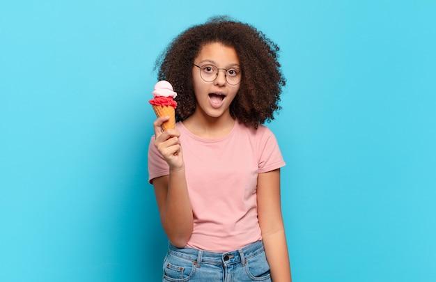 """Ładna nastolatka afro wyglądająca na bardzo zszokowaną lub zaskoczoną, patrząca z otwartymi ustami i mówiąca """"wow"""". koncepcja lodów sumer"""