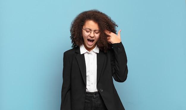 Ładna nastolatka afro wyglądająca na niezadowoloną i zestresowaną, gest samobójczy robiący znak pistoletu ręką, wskazujący na głowę. humorystyczna koncepcja biznesowa