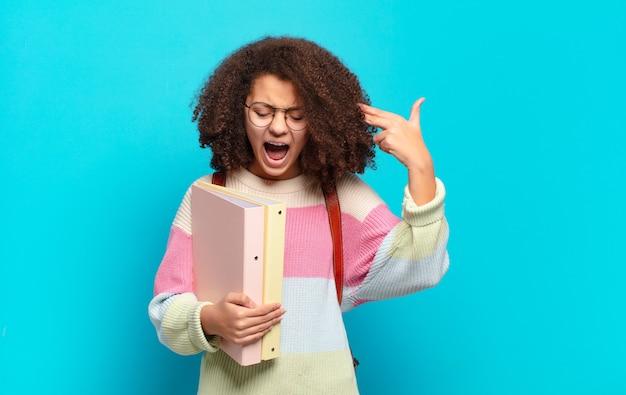 Ładna nastolatka afro wyglądająca na niezadowoloną i zestresowaną, gest samobójczy robiący znak pistoletu ręką, wskazujący na głowę. koncepcja studenta