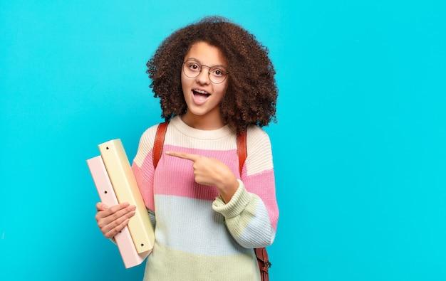 Ładna nastolatka afro wyglądająca na podekscytowaną i zaskoczoną, wskazując na bok i do góry, aby skopiować miejsce