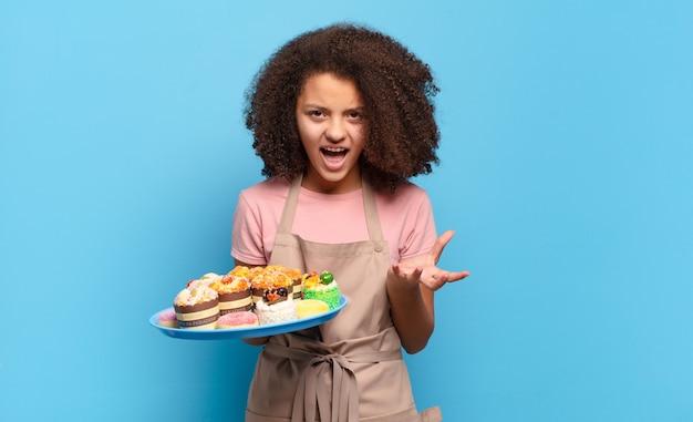 Ładna nastolatka afro wyglądająca na wściekłą, zirytowaną i sfrustrowaną krzyczącą wtf lub co jest z tobą nie tak. humorystyczny koncepcja piekarza
