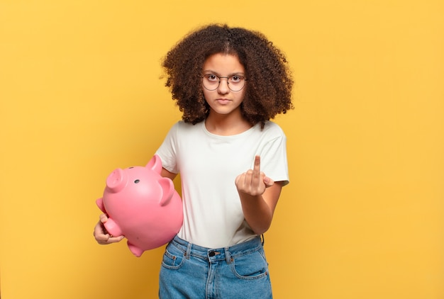 Ładna nastolatka afro wyglądająca na zaskoczoną i zszokowaną, z opuszczoną szczęką, trzymająca przedmiot z otwartą dłonią z boku. koncepcja oszczędności