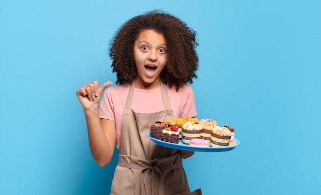 """Ładna nastolatka afro wyglądająca na zdziwioną z niedowierzaniem, wskazująca na przedmiot z boku i mówiąca """"wow, niewiarygodne"""". humorystyczna koncepcja piekarza"""