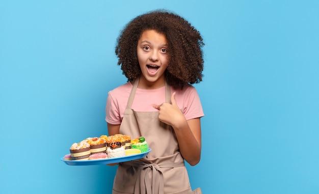 Ładna nastolatka afro wyglądająca na zszokowaną i zaskoczoną z szeroko otwartymi ustami, wskazując na siebie. humorystyczny piekarz