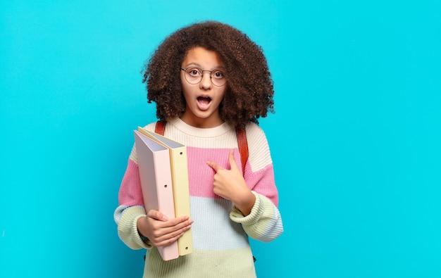 Ładna nastolatka afro wyglądająca na zszokowaną i zaskoczoną z szeroko otwartymi ustami, wskazując na siebie. koncepcja studenta