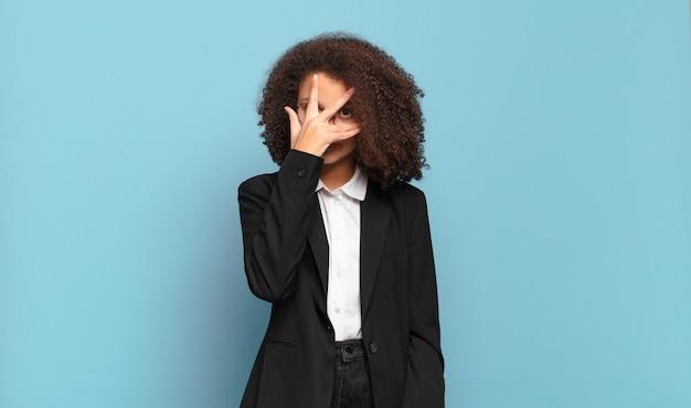 Ładna nastolatka afro wyglądająca na zszokowaną, przestraszoną lub przerażoną, zakrywającą twarz dłonią i zaglądającą między palce. humorystyczny pomysł na biznes