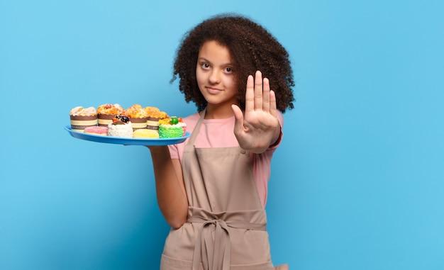 Ładna nastolatka afro wyglądająca poważnie, surowo, niezadowolona i wściekła pokazuje otwartą dłoń wykonującą gest stop. humorystyczny koncepcja piekarza