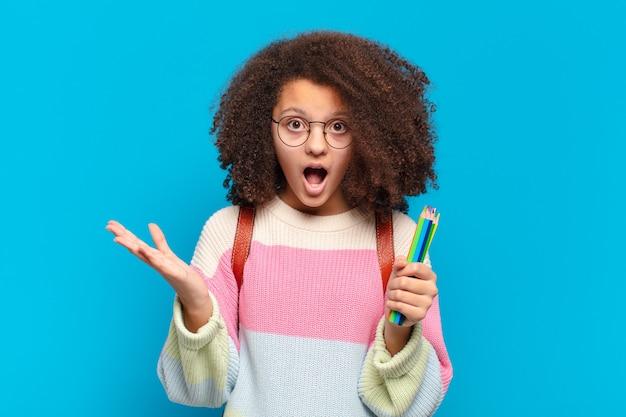 Ładna nastolatka afro z otwartymi ustami i zdumieniem, zszokowana i zdumiona niewiarygodną niespodzianką. koncepcja studenta