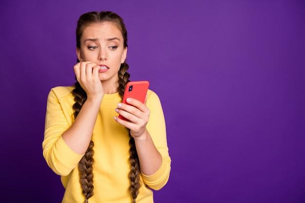 Ładna nastolatka pani długie warkocze trzymając telefon czyta okropne wiadomości zmartwiony zerwanie chłopaka nosić dorywczo żółty sweter na białym tle fioletowy kolor ściany