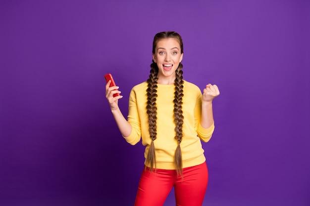Ładna nastolatka pani długie warkocze trzymając telefon szczęśliwy nosić na co dzień żółty sweter na białym tle fioletowy kolor ściany