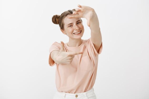 Ładna nastolatka pozuje na białej ścianie