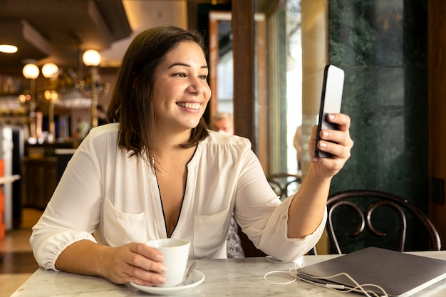 Ładna nastolatka przegląda swój telefon komórkowy