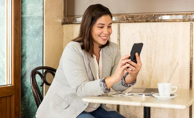 Ładna nastolatka przegląda swój telefon