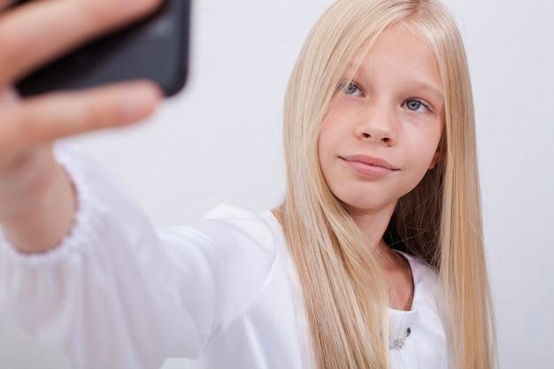 Ładna nastolatka robi selfie swoim smartfonem