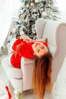 Ładna nastolatka w czerwonym swetrze relaksuje się w fotelu w pobliżu choinki