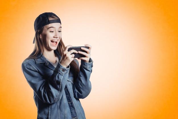 Ładna nastolatka w dżinsowej kurtce na pomarańczowej ścianie, grając w gry