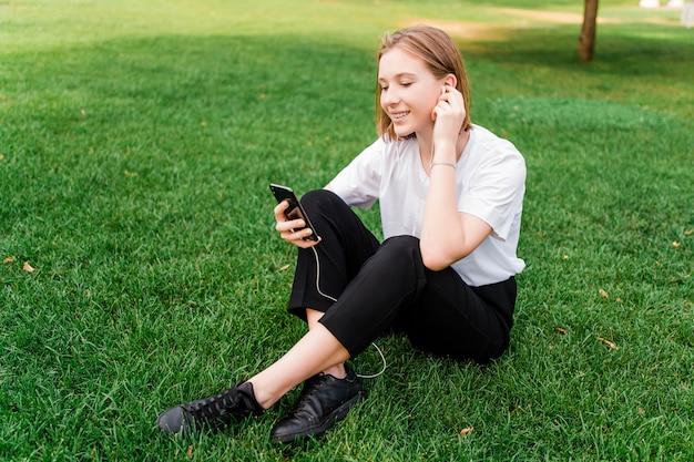 Ładna nastolatka w parku słucha muzyki przez słuchawki, siedząc na trawie