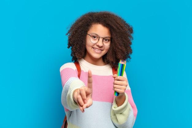 Ładna nastolatka w stylu afro, uśmiechająca się dumnie i pewnie w triumfującej pozie numer jeden