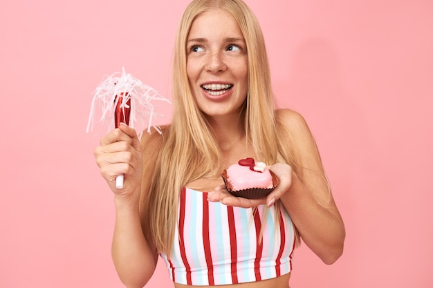 Ładna nastolatka z prostymi włosami i aparatami ortodontycznymi na zębach świętuje urodziny, pozuje odizolowana z dmuchawą imprezową i słodkim deserem, życząc sobie życzenia, z marzycielskim radosnym wyrazem twarzy
