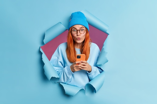 Ładna nastolatka z rudymi włosami czyta posty w sieciach społecznościowych rozmawia przez internet używa telefonu komórkowego wstrzymuje oddech wygląda zdziwiona używa nowoczesnego gadżetu ubranego w stylowe ubranie przebija papierową ścianę