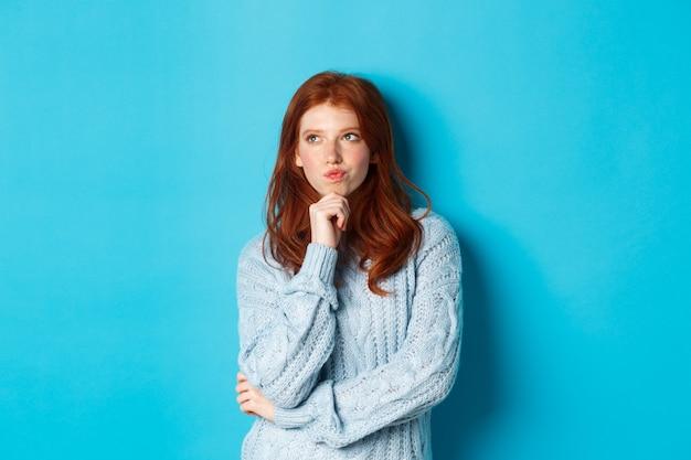 Ładna nastolatka z rudymi włosami myśli, zamyślona w lewym górnym rogu, rozważająca coś, stojąca na niebieskim tle.