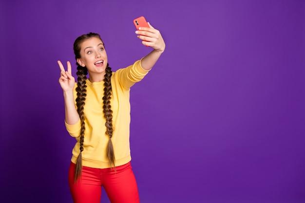 Ładna nastoletnia dama z długimi warkoczami trzymając telefon robiąc selfie z symbolem v-sign nosić dorywczo żółty sweter czerwone spodnie na białym tle fioletowy kolor ściany