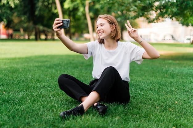 Ładna nastoletnia dziewczyna robi selfie w parku na trawie
