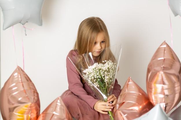 Ładna niebieskooka blond dziewczyna w sukience trzyma bukiet białych kwiatów