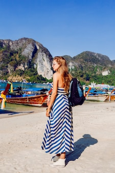 Ładna opalona dziewczyna z plecakiem pozująca na gorącej tropikalnej wyspie phi phi, niesamowity widok na lokalne łodzie i góry.