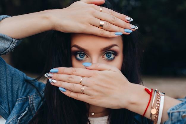 Ładna pani chowająca się za rękami z niebieskimi i białymi paznokciami