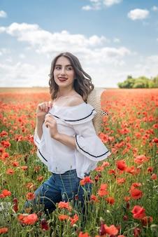 Ładna pani cieszyć się wolnym czasem na polu czerwonego maku, słoneczny dzień. zdrowy tryb życia