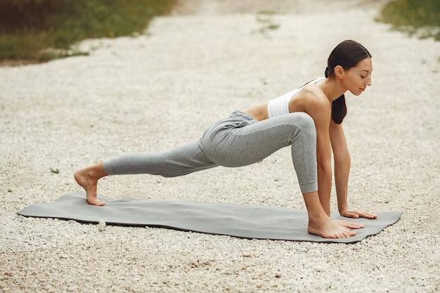 Ładna pani trenująca na letniej plaży. brunetka robi joga. dziewczyna w stroju sportowym.