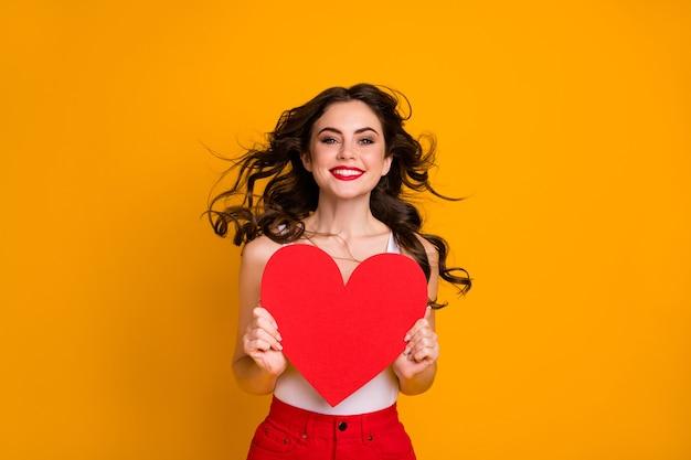Ładna pani trzyma dużą papierową pocztówkę serca